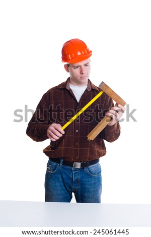 Portrait of an engineer in helmet making measurements using roulette, isolated on white background