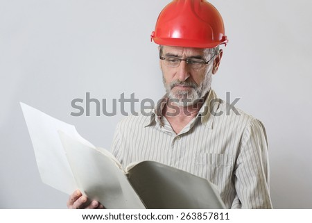 Portrait of an engineer, Portrait of an engineer with helmet and project papers, studio shoot - stock photo