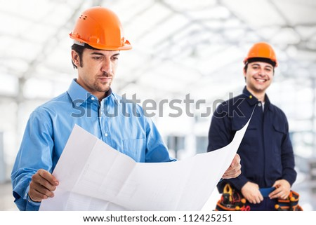 Portrait of an engineer reading a blueprint - stock photo