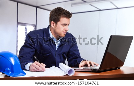 Portrait of an engineer using a notebook in the site office - stock photo