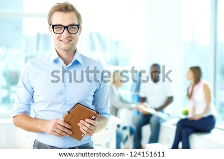 Portrait of an enthusiastic businessman with a team in the background - stock photo