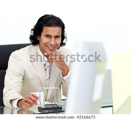 Portrait of an ethnic businessman having fun with kinetic balls in the office - stock photo