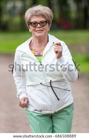 Portrait of an European woman in a tracksuit while jogging in park