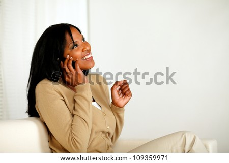 Portrait of an excited afro-American woman conversing on mobile phone while sitting on couch at home indoor - stock photo