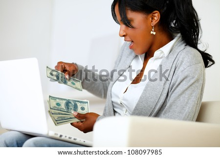 Portrait of an excited ambitious afro-american woman with dollars while is sitting on sofa at home in front a laptop - stock photo