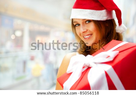 Portrait of an excited attractive woman with red box and white ribbon standing at shopping mall and daydreaming. She is wearing Santa`s hat and preparing gifts for christmas.