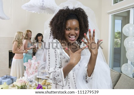 Portrait of an excited bride showing her engagement ring with friends celebrating  party in the background