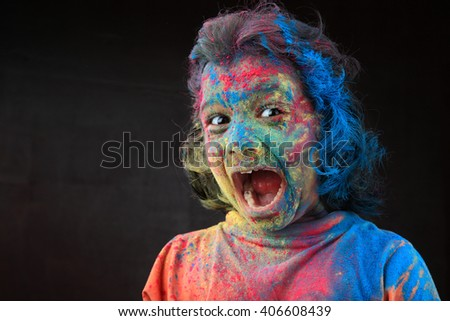 Portrait of an excited  girl with face smeared with colors in a dark background. Concept for Indian festival Holi. - stock photo
