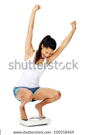 portrait of an excited hispanic woman on a scale who has lost weight and is fit and healthy - stock photo