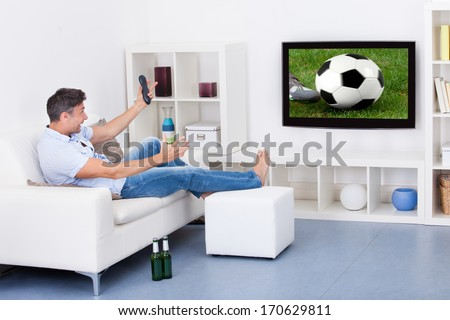 Portrait Of An Excited Mature Man Watching Soccer Game On Television - stock photo