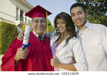 Portrait of an excited senior male graduate with family holding degree - stock photo