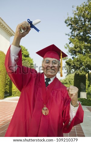 Portrait of an excited senior man in graduation attire holding degree - stock photo