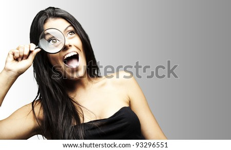 portrait of an excited woman looking through a magnifying glass over a grey background - stock photo