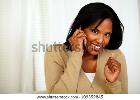 Portrait of an excited woman looking to you and conversing on mobile phone at home indoor - stock photo
