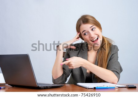 Portrait of an excited young female business executive while pointing at the screen of laptop - stock photo