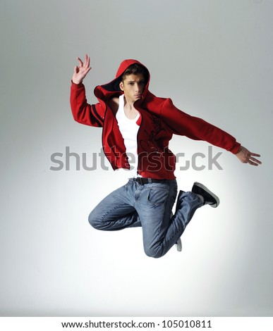 Portrait of an excited young man jumping in air against light background - stock photo