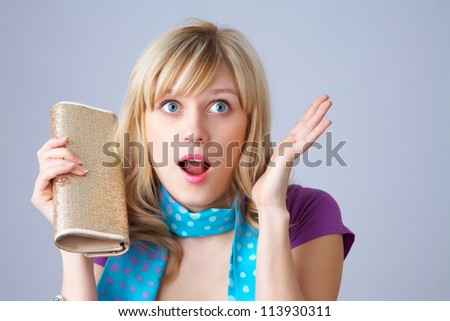 Portrait of an excited young woman against grey background - stock photo