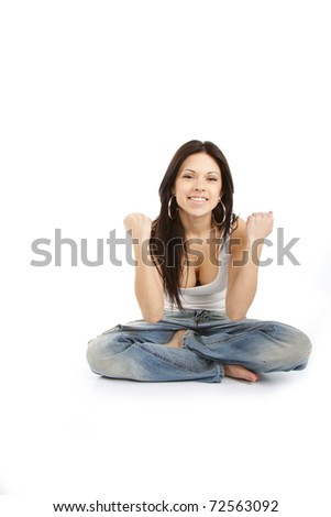 Portrait of an excited young woman gesturing yes sign against white background in yoga pose - stock photo
