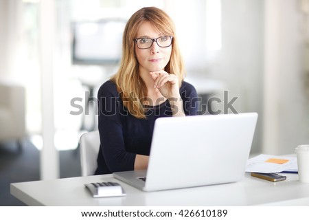 Portrait of an executive investment advisor professional woman sitting at office and working on laptop. - stock photo