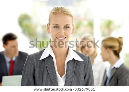 Portrait of an Executive woman on foreground with staff at meeting in the background - stock photo