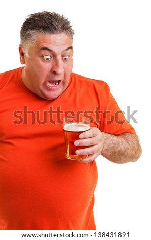 Portrait of an expressive fat man staring at a glass of beer isolated on white background
