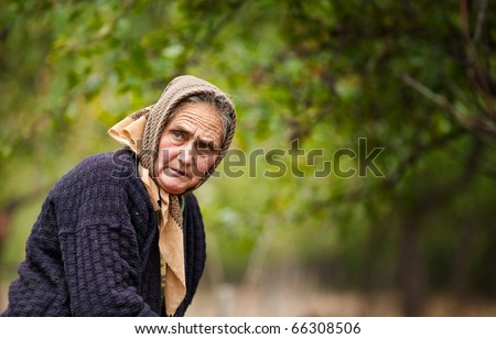 Portrait of an expressive old woman outdoor in an orchard - stock photo