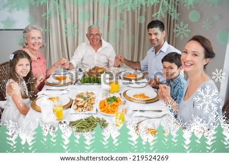 Portrait of an extended family at dining table against snowflakes and fir trees in green