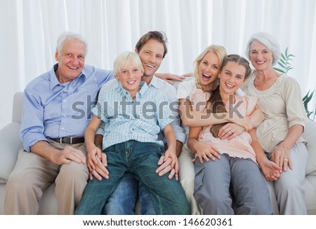 Portrait of an extended family sitting on couch and smiling at camera
