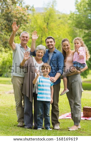 Portrait of an extended family waving hands in the park
