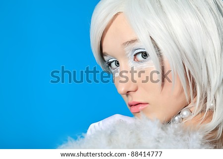 Portrait of an extravagant blonde model over blue background.