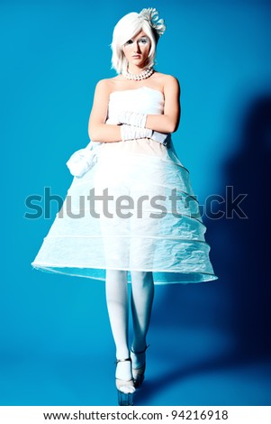 Portrait of an extravagant blonde model over blue background. - stock photo