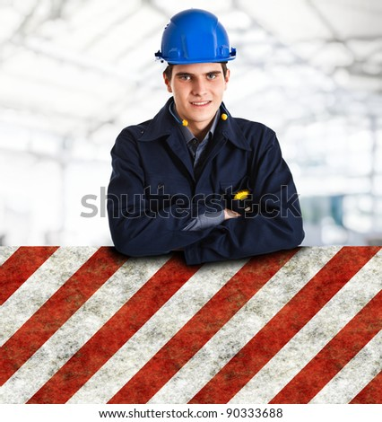 Portrait of an handsome engineer leaning on a sign