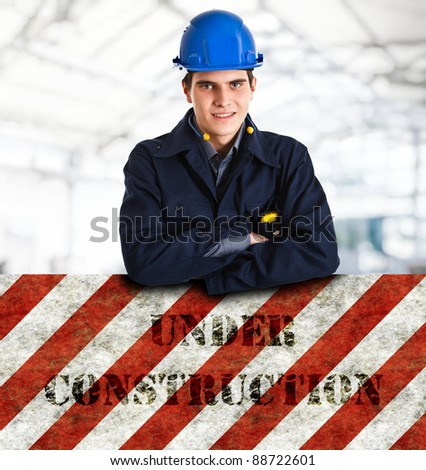 """Portrait of an handsome engineer leaning on a """"Under construction"""" sign - stock photo"""