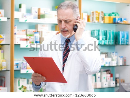 Portrait of an handsome senior pharmacist in his shop - stock photo