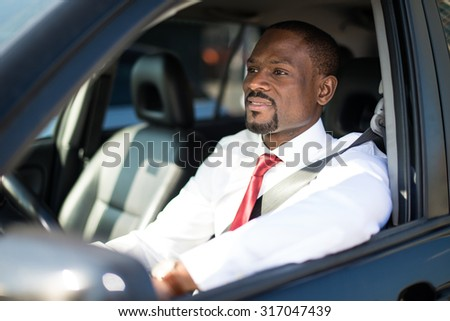 Portrait of an handsome smiling business man driving his car - stock photo