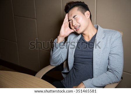 Portrait of an handsome smiling young business man in working room serious style