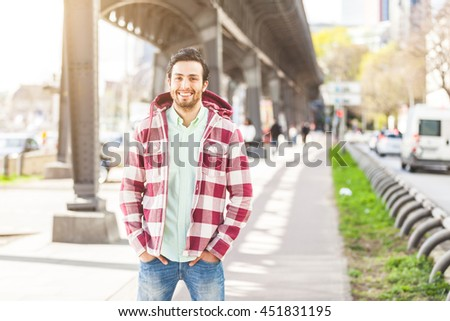 Portrait of an handsome young man in Hamburg. He is middle eastern, on his early twenties. He is looking at camera and smiling. Real people portrait with candid expression