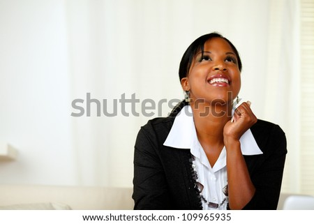 Portrait of an happy afro-American woman looking up on black suit at soft colors composition - stock photo