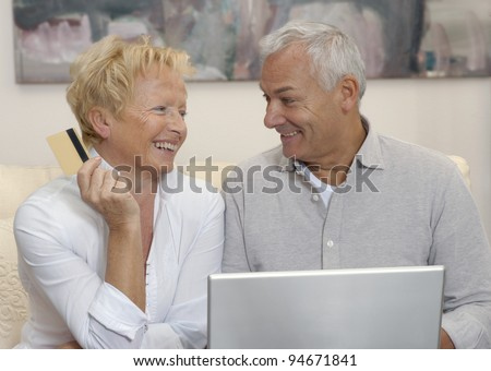 Portrait of an happy aged couple shopping on line using laptop - stock photo