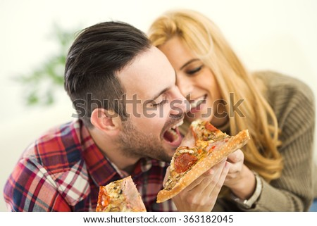 Portrait of an happy couple.They are laughing and eating pizza and having a great time. - stock photo