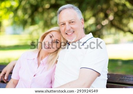 Portrait of an happy mature couple sitting in a park