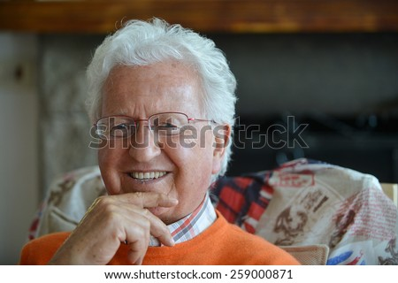 Portrait of an happy old man in his house - stock photo