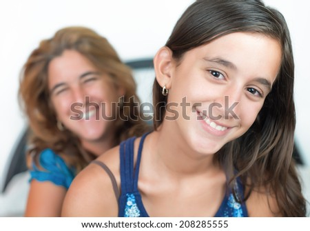 Portrait of an hispanic young girl and her mother smiling at home - stock photo