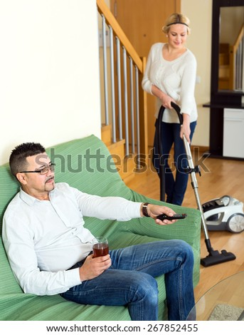 Portrait of an ideal couple in a living room indoors: boyfriend sitting on a sofa with a glass of beer watching TV and his girlfriend is cleaning their apartment - stock photo