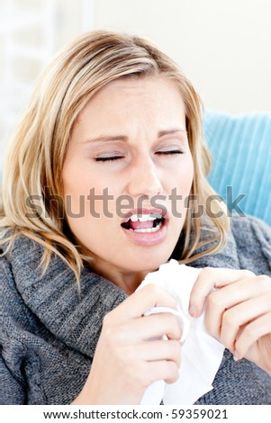 Portrait of an ill woman blowing lying on a sofa against white background - stock photo