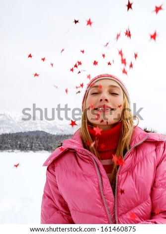 Portrait of an imaginative, young and beautiful woman in the snow mountains landscape throwing star shaped glitter up in the sky during a cold Christmas winter day outdoors in nature. - stock photo