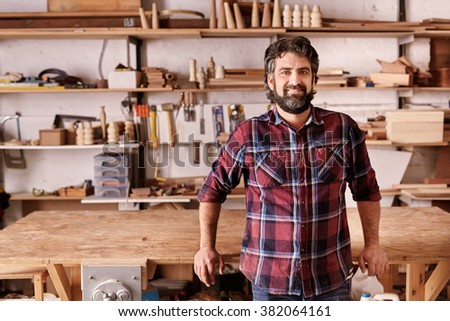 Portrait of an independent designer in his furniture manufacturing workshop, leaning against the edge of his workbench, looking relaxed and confident - stock photo