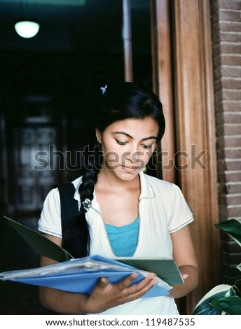 Portrait of an Indian / Asian female student coming out of the examination hall in the campus. - stock photo