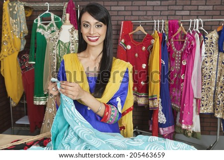 Portrait of an Indian female dressmaker working at design studio - stock photo