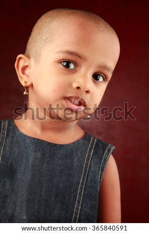 Portrait of an Indian girl child with shaved head - stock photo